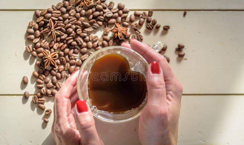 A bebida quente aérea com ` s da mulher entrega guardar o copo foto de stock