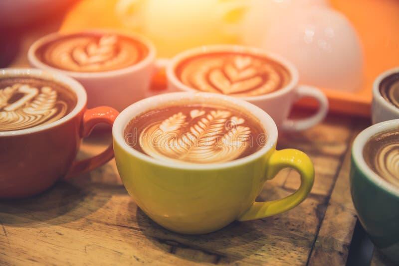 A bebida quente popular da arte do latte do café serviu na tabela de madeira fotos de stock royalty free