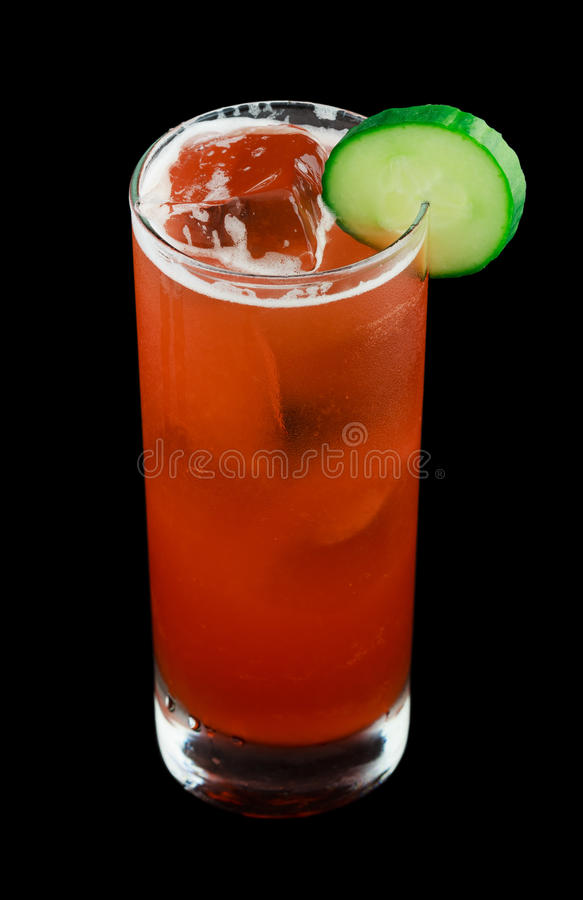 Bebida roja con una rebanada del pepino aislada en negro imagen de archivo