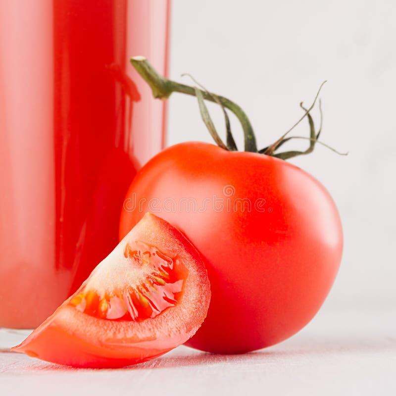 Bebida saudável do vegetariano - suco de tomate fresco com fatia na placa de madeira branca, espaço da cópia, macro, quadrado foto de stock royalty free