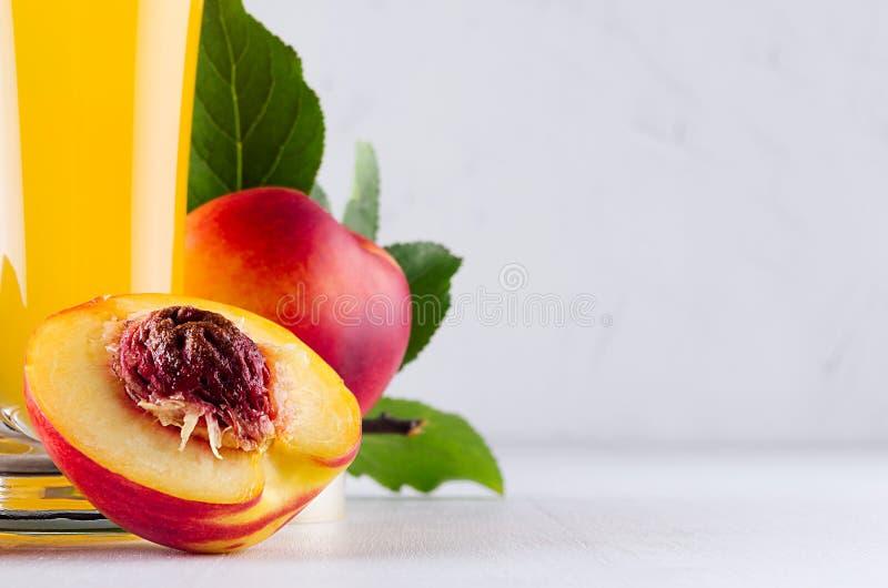 Bebida saudável - suco fresco das nectarina e dos ingredientes - meia nectarina com o close up da semente na placa de madeira bra fotografia de stock royalty free