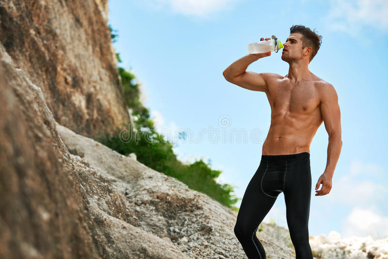 Bebida sedento quente da água potável do homem após a corrida fora esporte foto de stock royalty free