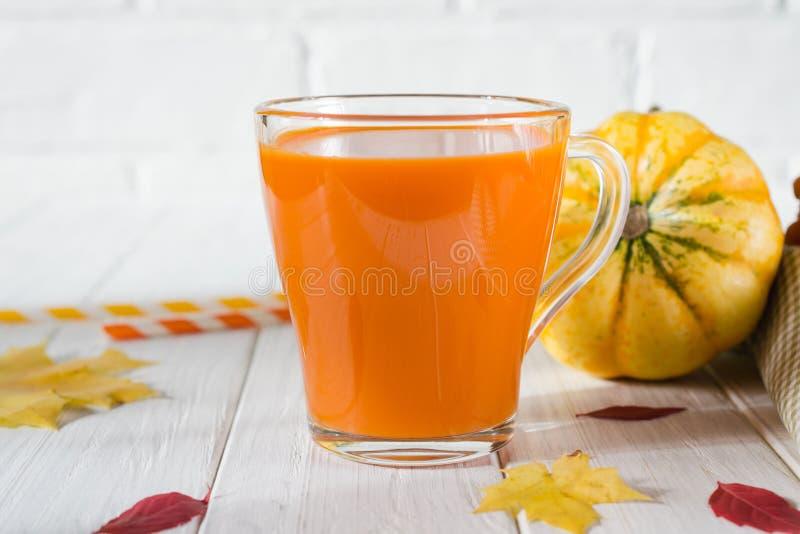 Bebida tradicional del otoño Tazas de cristal de jugo de la calabaza, de calabazas y de hojas caidas fotografía de archivo