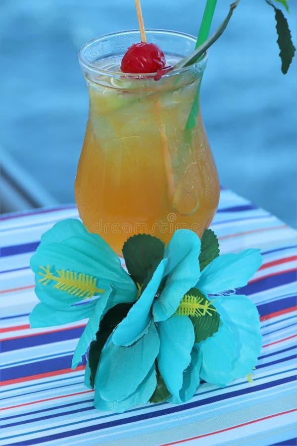 Bebida tropical con la fruta y el fondo azul del océano imagenes de archivo