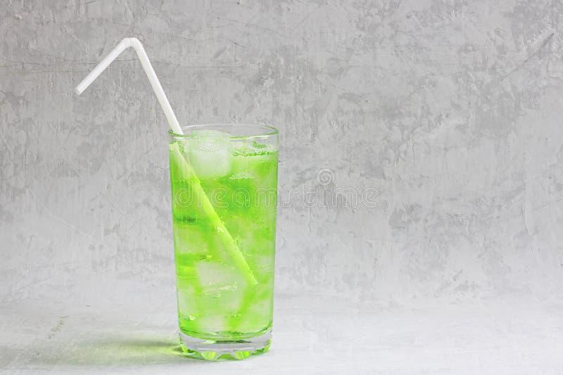 Bebida verde fría del verano con la cal, menta y limón en vidrio alto con hielo y paja y fruta defocused alrededor en gris fotos de archivo
