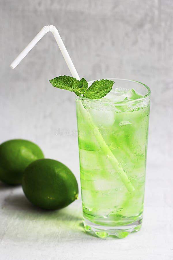 Bebida verde fría del verano con la cal, menta y limón en vidrio alto con hielo y paja y fruta defocused alrededor en gris fotografía de archivo libre de regalías