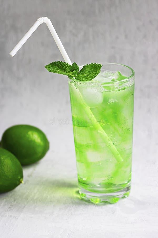 Bebida verde fría del verano con la cal, menta y limón en vidrio alto con hielo y paja y fruta defocused alrededor en gris fotografía de archivo