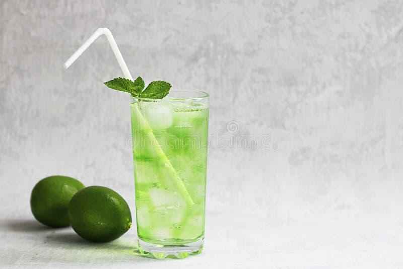Bebida verde fría del verano con la cal, menta y limón en vidrio alto con hielo y paja y fruta defocused alrededor en gris foto de archivo