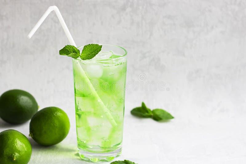 Bebida verde fría del verano con la cal, menta y limón en vidrio alto con hielo y paja y fruta defocused alrededor en gris imagen de archivo libre de regalías