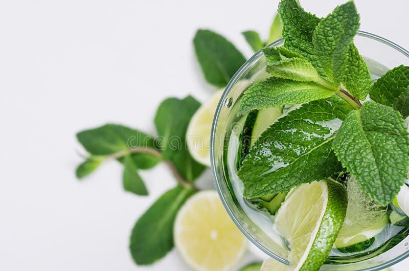 Bebida verde fria da mola com pepino, partes de cal, as folhas frescas hortelã e os cubos de gelo no fundo branco macio imagens de stock royalty free