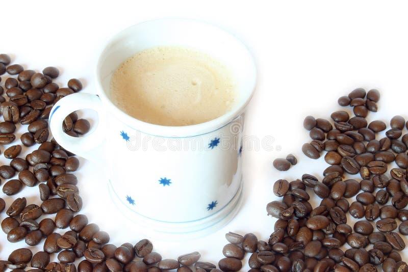 Bebida y alimento - taza de café con las habas imagen de archivo
