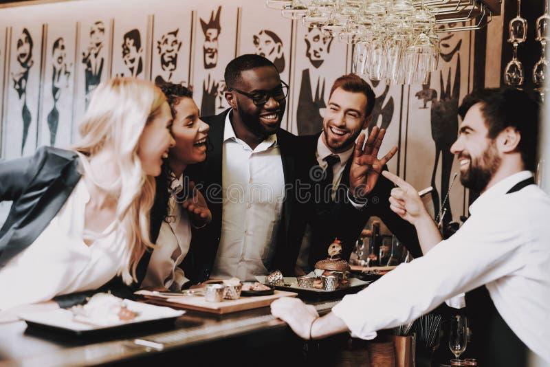 Bebidas alcoólicas da bebida Homem e mulheres felizes alegre imagem de stock royalty free