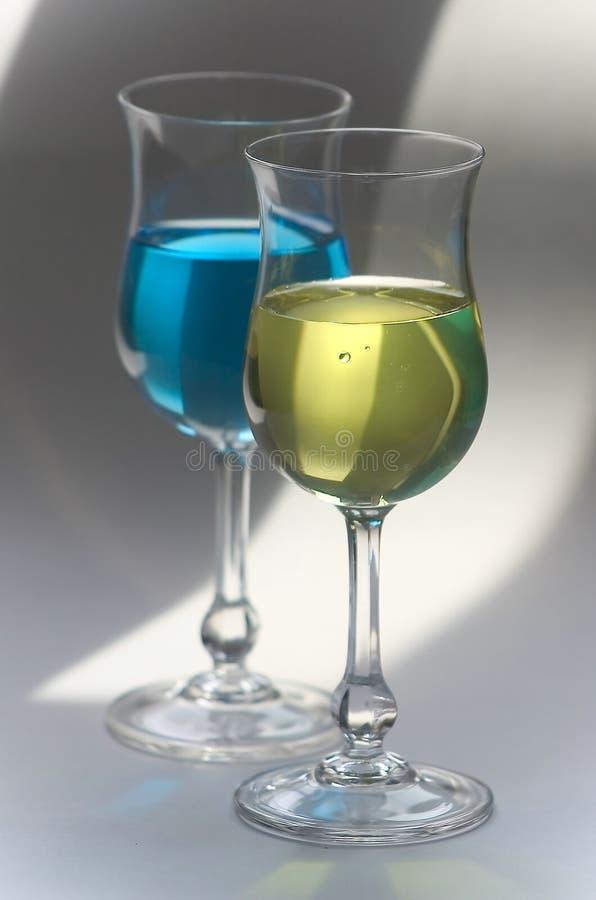 Bebidas amarillas y del azul en vidrios foto de archivo