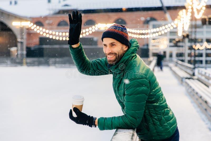 Bebidas barbudas sonrientes café para llevar, ondas del varón con la mano a fotografía de archivo
