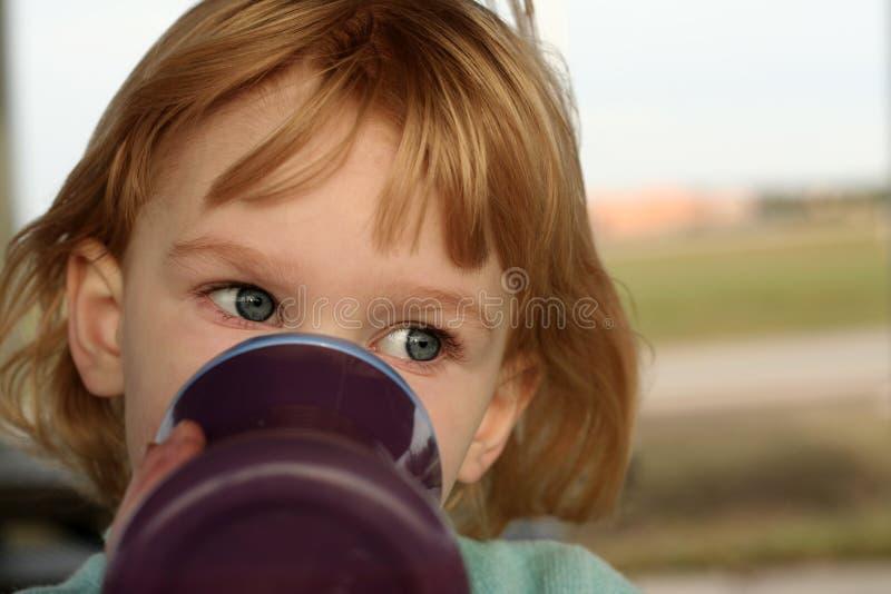 Bebidas de la muchacha de la taza sippy fotografía de archivo