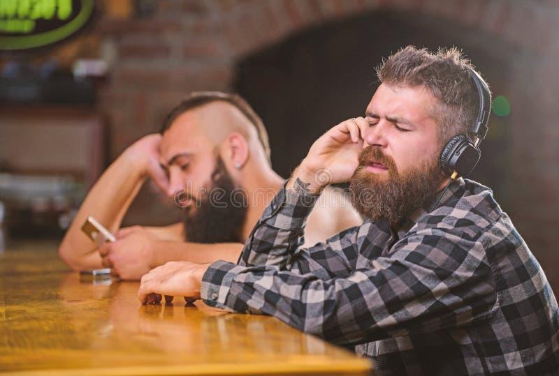 Bebidas de la orden en el contador de la barra Hombres con los auriculares y smartphone que se relaja en la barra Evite la comuni imágenes de archivo libres de regalías