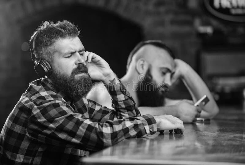 Bebidas de la orden en el contador de la barra Hombres con los auriculares y smartphone que se relaja en la barra Evite la comuni imagen de archivo libre de regalías