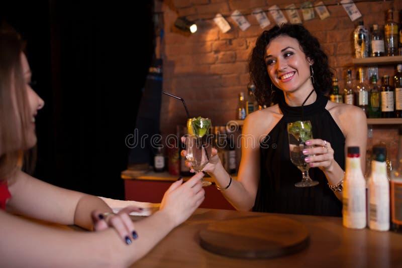 Bebidas de ofrecimiento bastante sonrientes del camarero de sexo femenino a las huéspedes que se colocan detrás de contador de la fotografía de archivo libre de regalías