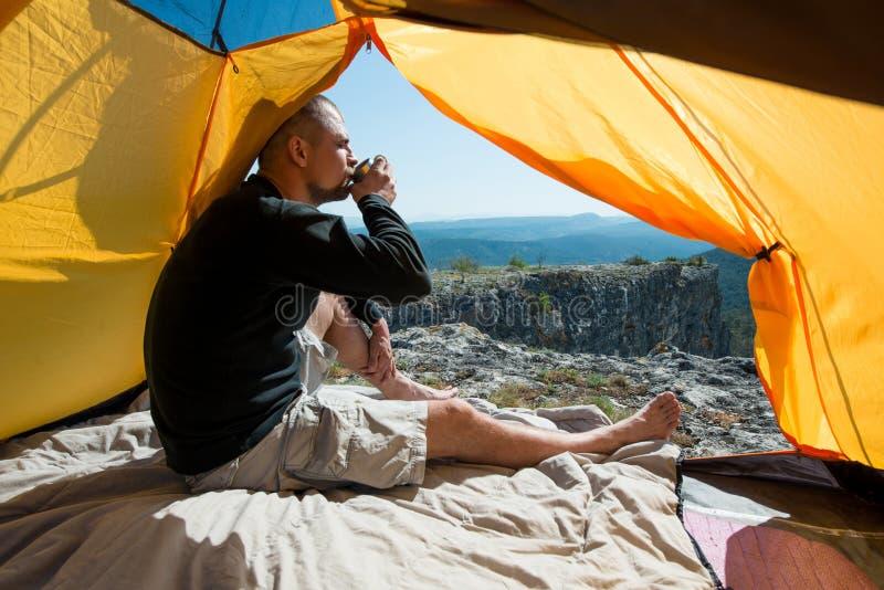Bebidas del hombre de una taza en acampar al aire libre fotografía de archivo libre de regalías