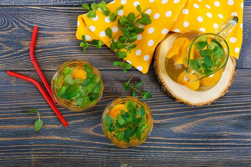 Bebidas do frio do verão Bebida de refrescamento deliciosa com abricó e hortelã nos vidros em uma tabela de madeira Compota dos f imagens de stock royalty free