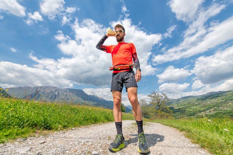 Bebidas do homem de uma garrafa de água durante uma fuga nas montanhas fotos de stock royalty free
