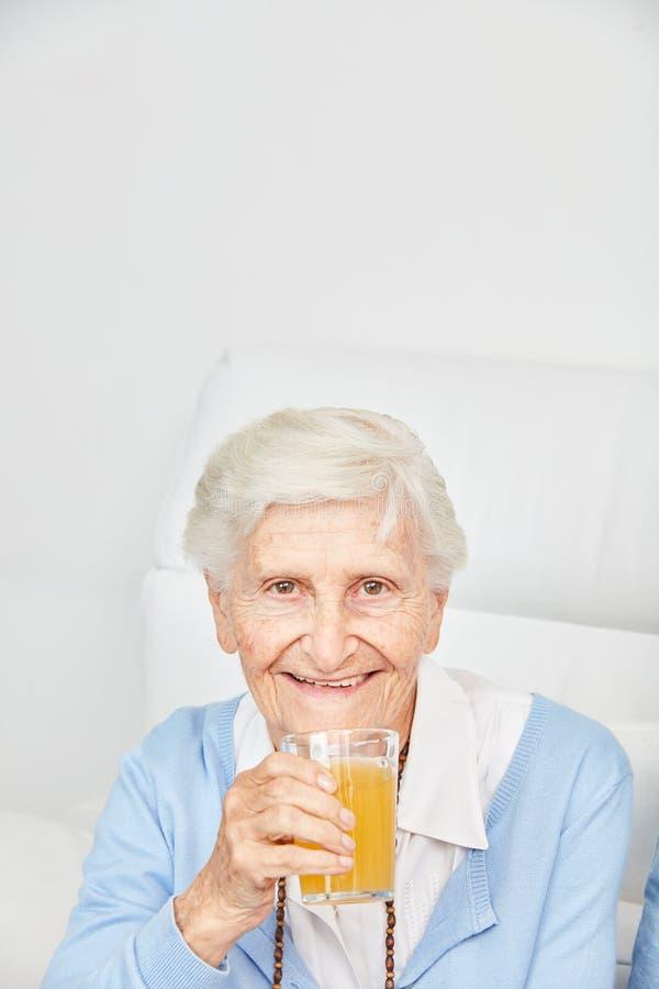 Bebidas do idoso um o vidro do suco de laranja fotos de stock royalty free