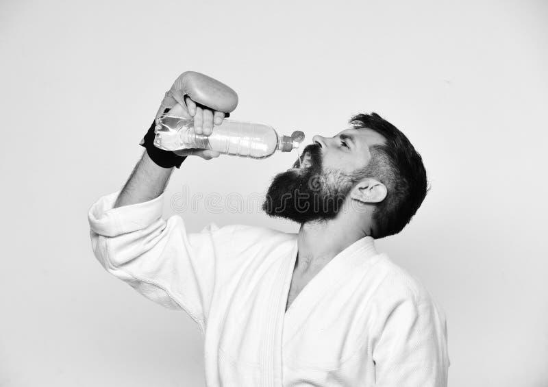 Bebidas do mestre do combate que refrescam a água após a formação Homem com a barba no quimono no fundo branco Exercício e imagem de stock royalty free