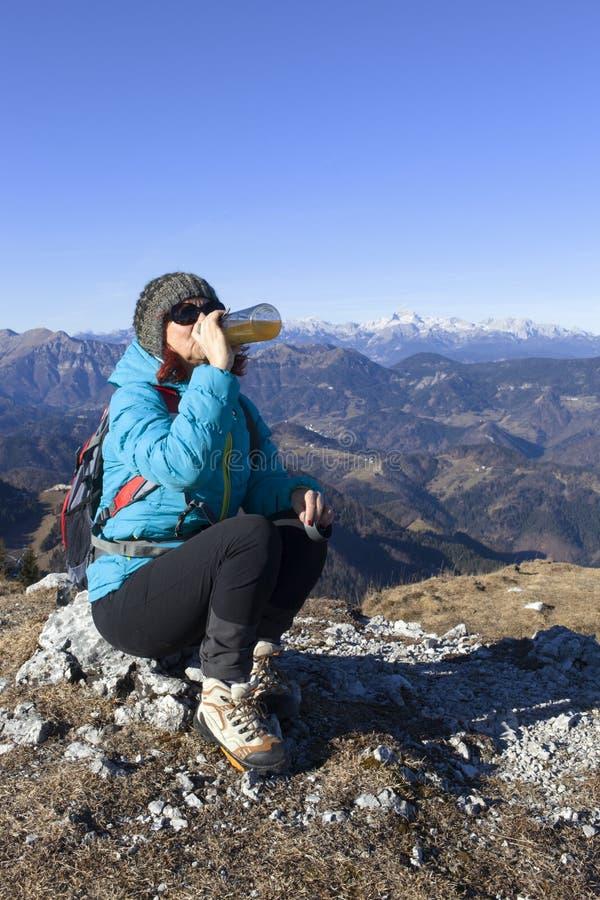 Bebidas do trekker da mulher nas montanhas imagem de stock