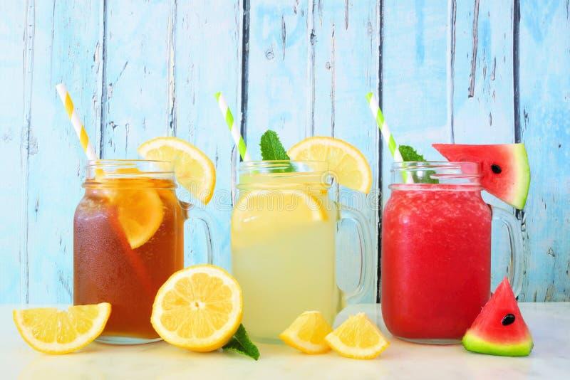 Bebidas do verão do suco do chá gelado, da limonada e da melancia em vidros do frasco de pedreiro contra a madeira azul fotografia de stock