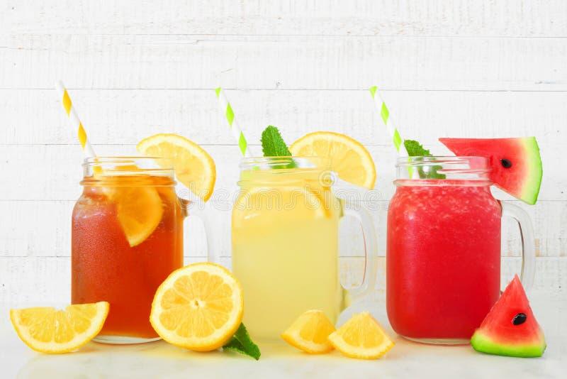 Bebidas do verão do suco do chá gelado, da limonada e da melancia em vidros do frasco de pedreiro contra a madeira branca fotografia de stock royalty free