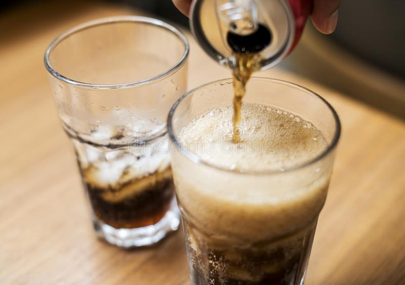 Bebidas efervescentes de derramamento no vidro imagens de stock royalty free