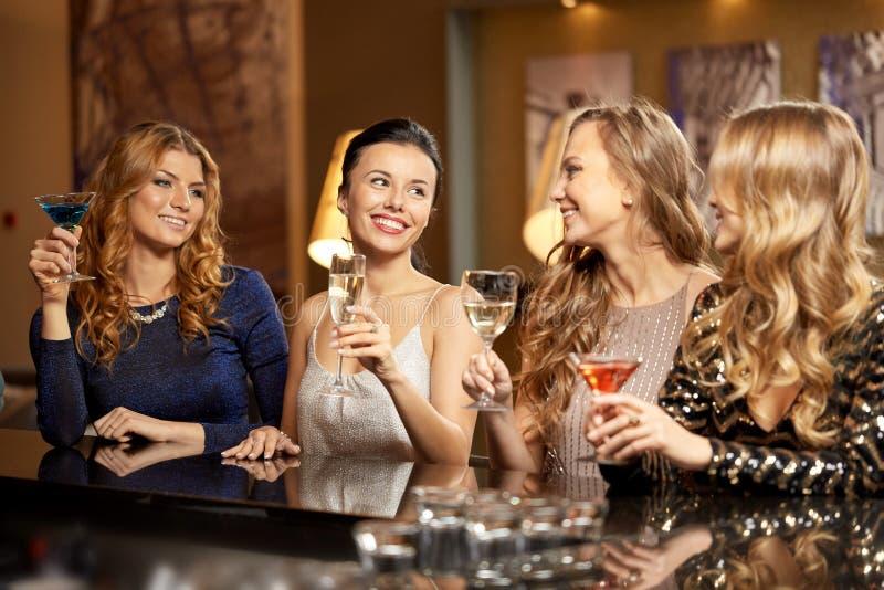 Bebidas felizes das mulheres nos vidros no clube noturno imagens de stock