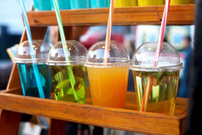 Bebidas frias do verão colorido em uns copos plásticos na exposição fotos de stock royalty free