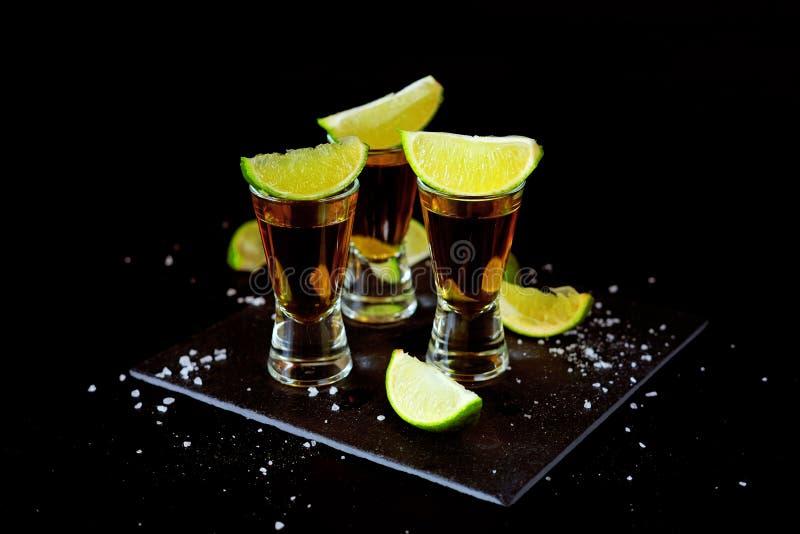 Bebidas fuertes del alcohol Tiros del Tequila con las rebanadas de la sal y de la cal imágenes de archivo libres de regalías