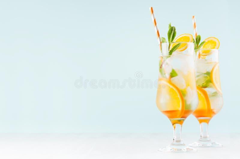 Bebidas sanas frías de la fruta cítrica con la naranja, menta verde, hielo, paja en vidrio misted en interior azul moderno en la  foto de archivo