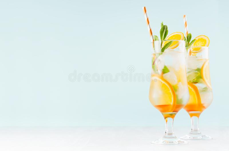 Bebidas saudáveis frias do citrino com laranja, hortelã verde, gelo, palha no vidro misted no interior azul moderno na tabela de  foto de stock
