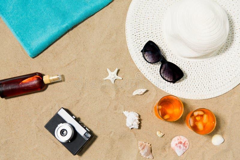Bebidas, sombrero, cámara y gafas de sol en la arena de la playa imagen de archivo libre de regalías