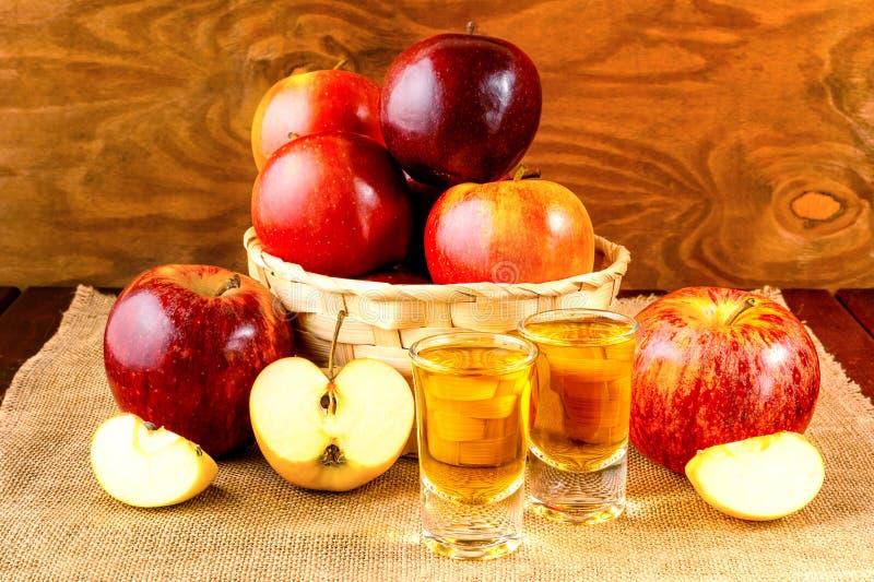 Bebidas y manzanas del aguardiente en la cesta de mimbre imágenes de archivo libres de regalías