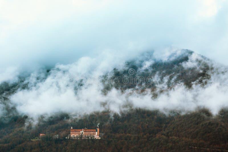 Beboste die berghelling in mist wordt gehuld stock afbeeldingen
