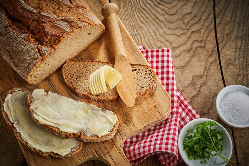 Beboterde plakken van roggebrood met kommen peterselie stock foto's