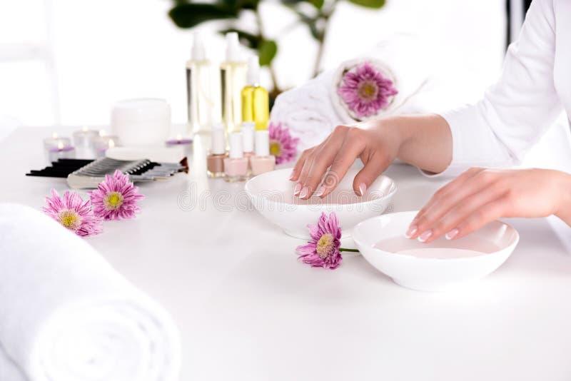 bebouwd beeld die van vrouw bad voor spijkers ontvangen bij lijst met bloemen, handdoeken, kaarsen, de flessen van de aromaolie,  royalty-vrije stock foto