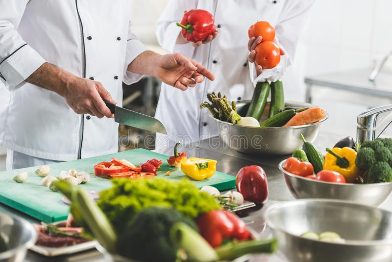 bebouwd beeld van chef-koks die groenten voorbereiden royalty-vrije stock afbeelding