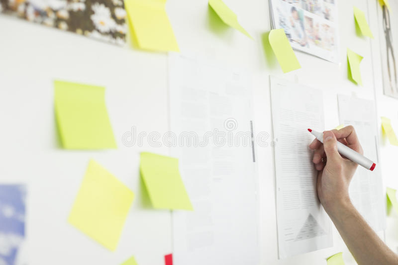 Bebouwd beeld van de hand die van de zakenman op papier in bureau schrijven stock afbeeldingen