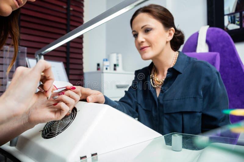 Bebouwd Beeld van de Hand van de Cliënt van Manicureperforming manicure on royalty-vrije stock afbeeldingen