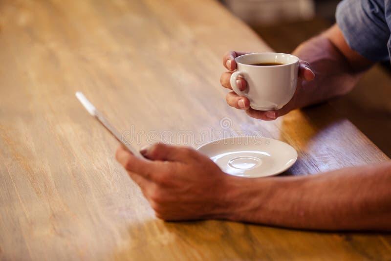 Bebouwd beeld van de hipstermens die smartphone gebruiken terwijl het drinken van kop van koffie royalty-vrije stock afbeelding