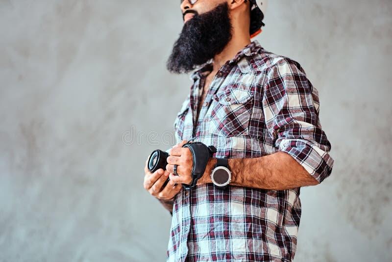 Bebouwd beeld van een gebaard mannetje die een geruit overhemd dragen die een camera houden stock afbeeldingen