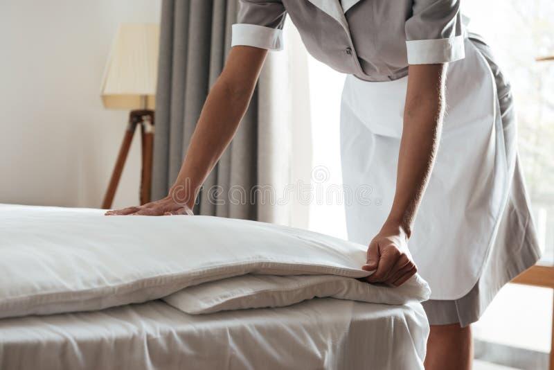 Bebouwd beeld van een kamermeisje die bed in hotelruimte maken royalty-vrije stock afbeeldingen