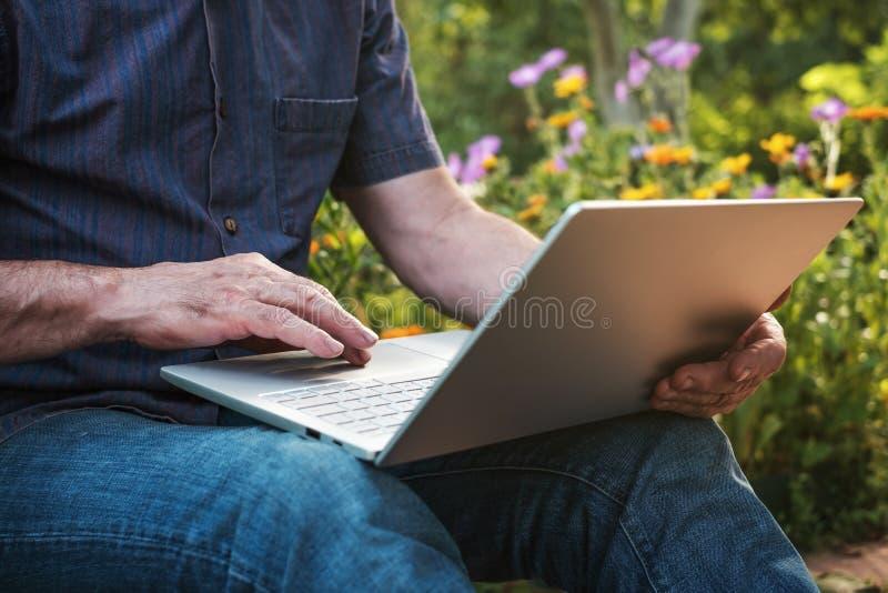 Bebouwd beeld van een rijpe mens die aan zijn laptop in tuin, oud mannetje werken die blogger op notitieboekje typen royalty-vrije stock foto