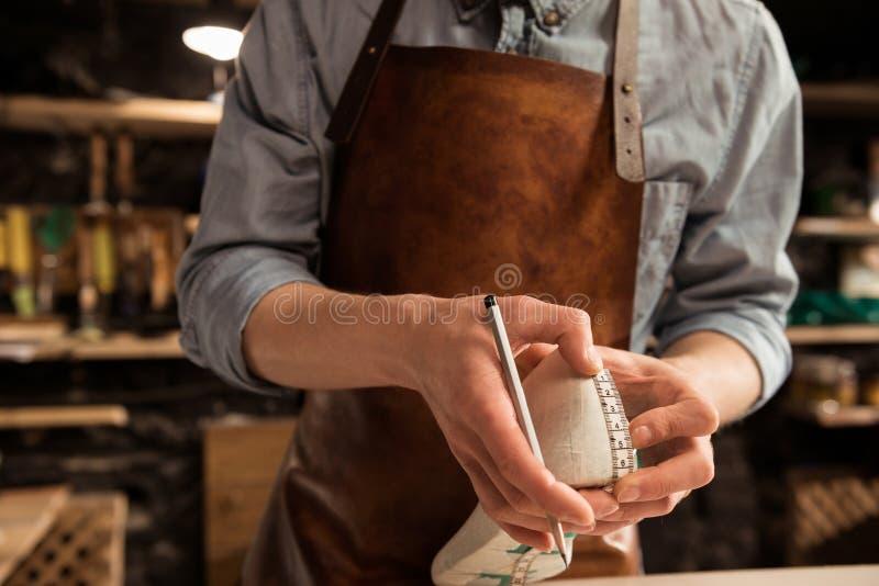 Bebouwd beeld van een schoenmaker die een schoen meten stock afbeeldingen