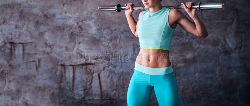 Bebouwd beeld van een vrouw in sportkledingstraining met een barbell in de gymnastiek tegen een grijze muur stock foto